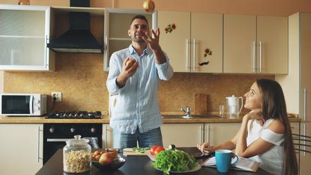 Aantrekkelijk houdend van paar dat pret in de keuken heeft. Knappe man goochelt met appels om indruk te maken op zijn vriendin