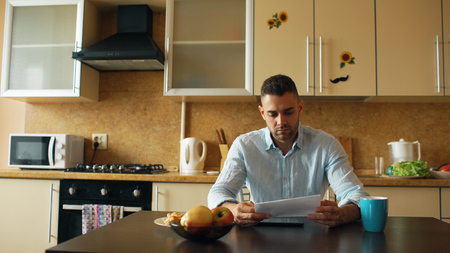 Upset young man reading letter with unpaid bill in the kitchen at home Stock Photo