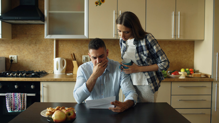 Upset young man reading unpaid bills and hugged by his wife supporting him in the kitchen at home Stock Photo