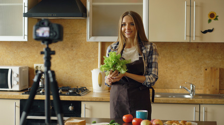 Young attractive woman in apron shooting video food blog about cooking on dslr camera in kitchen Stock Photo