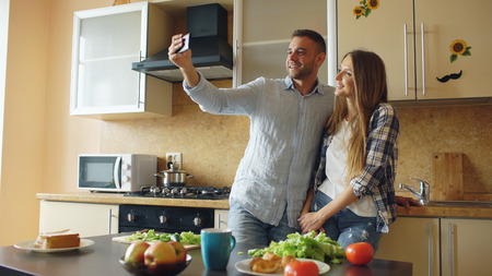 Young happy couple taking selfie picture while cooking breakfast in the kitchen at home