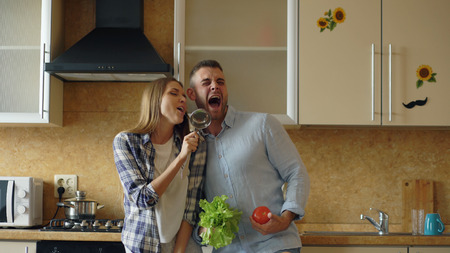 Attractive young joyful couple have fun dancing and singing while cooking in the kitchen at home Stockfoto