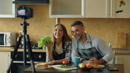 Young attractive couple shooting video food blog about cooking on dslr camera in the kitchen