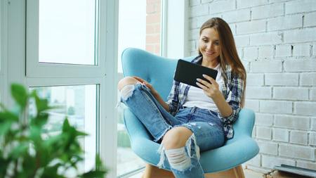 Joven mujer feliz tener video chat en línea utilizando equipo de tableta digital sentado en el balcón en loft apartamento moderno