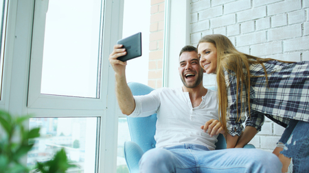 Young attractive couple having online video chat using tablet computer sitting at balcony in modern loft apartment Stock Photo