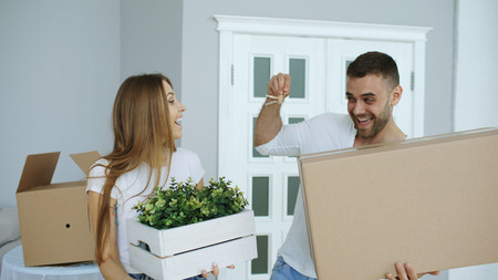 Happy couple watching their new home excited. Young man give keys to his girlfriend and kissing her Stock Photo