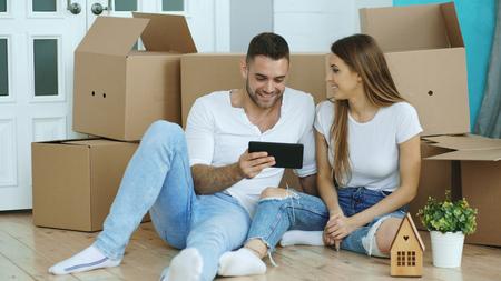 Jong koppel zittend op de vloer met behulp van tablet pc na relokatie in hun nieuwe huis