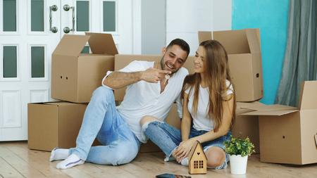 新しい家の床に座っている幸せなカップル。若い男は彼のガールフレンドに鍵を与え、彼女にキス