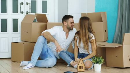 Happy couple sitting on floor in new house Stock Photo