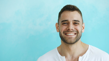 Closeup portrait of young smiling and laughing man looking into camera on blue background