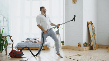 Young man having fun cleaning house with vacuum cleaner dancing like guitarist Stock Photo - 91616939