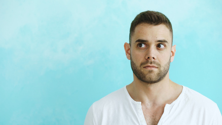 Portrait of young handsome man grimacing into camera and show different emotions on blue background Imagens