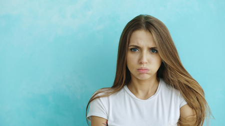 Portrait of angry young woman looking into camera nervous on blue background Stock Photo