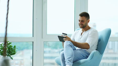 Young smiling man doing online shopping using digital tablet computer sitting at balcony in modern loft apartment Banque d'images