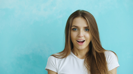 Portrait of young woman actively surprising and wondering looking into camera on blue background Stock Photo