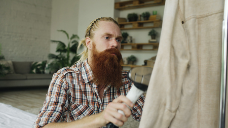 Bearded man steaming his jacket in bedroom at home