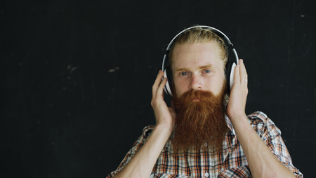 Closeup portrait of bearded young man in headphones listen to music and looking into camera smiling