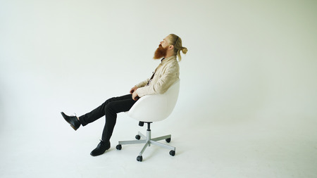 Smiling bearded man turning on swivel office chair on white background 스톡 콘텐츠