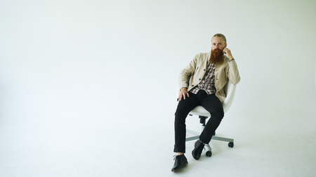 Serious bearded man sitting on swivel office chair and looking into camera on white background Stock fotó