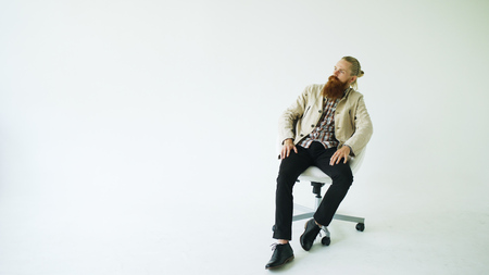 Serious bearded man sitting on swivel office chair on white background Stock Photo