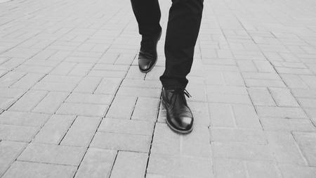 Closeup view businessman in shoes walking ahead sidewalk at street
