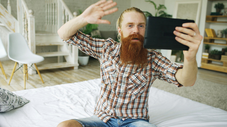 Young bearded man using tablet computer having video chat sitting in bed at home Фото со стока