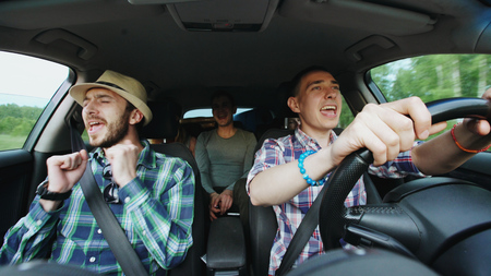 Group of happy friends in car singing and dancing while drive road trip Archivio Fotografico