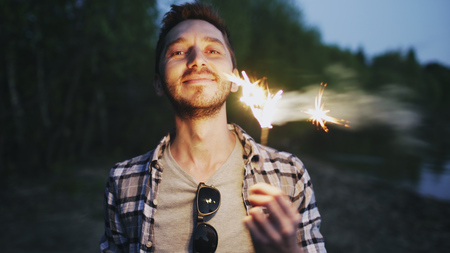 Portrait of young smiling man with sparkler celebrating at beach party Stock Photo