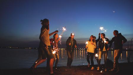 Grupo de jóvenes amigos que tienen una fiesta en la playa. Amigos bailando y celebrando con estrellitas en el crepúsculo del atardecer