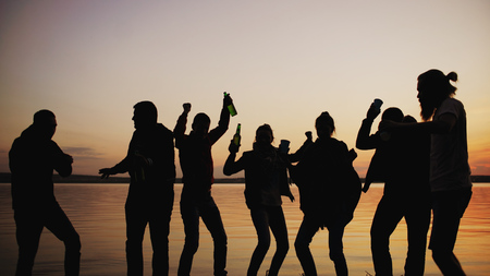 Silhouette of Group young dancing people have a party at beach on sunset Archivio Fotografico