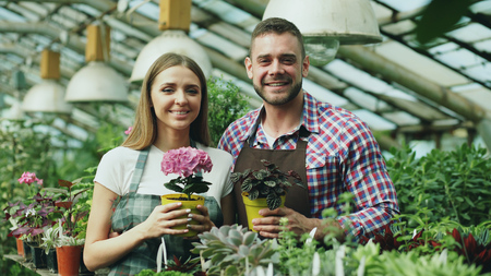 Happy young couple smiling in greenhouse. Attractive woman and man florists in apron work in garden looking into camera