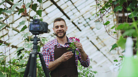 Young smiling blogger man florist in apron holding flower talking and recording video blog for his online vlog about gardening Stock Photo