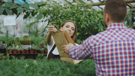Young smiling seller florist working in garden center. Woman gives shopping bag to customer at store Stock Photo