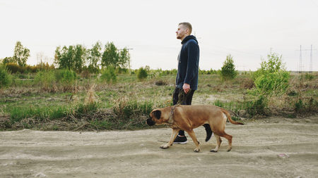Young sporty man walking with his bullmastiff dog outdoor at nature after crossfit training Reklamní fotografie - 91629011