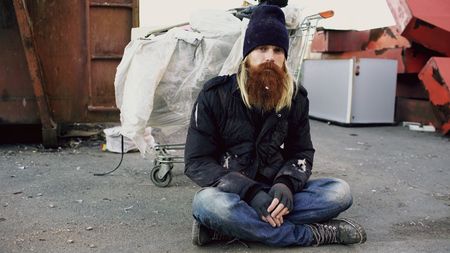 Portrait of young bearded homeless man sitting on a sidewalk near shopping cart ang garbage container during cold winter day