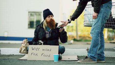 Jonge man helpt dakloze persoon en geeft hem wat te eten terwijl bedelaar alcohol drinkt en in de buurt van het winkelwagentje op straat zit