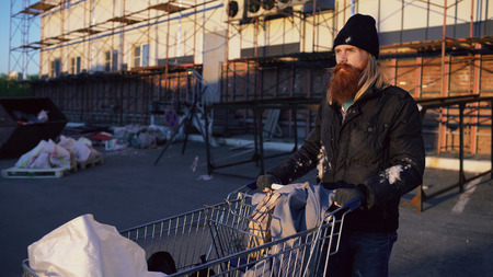 bearded homeless man walking down the street with shooping card at cold autumn day