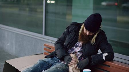 Betrunkener obdachloser betrunkener Mann , der auf Bank auf dem Bürgersteig sitzt Standard-Bild - 91628370