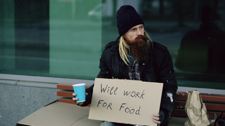 Homeless young man beg for money shaking cup to pay attention people walking near beggar at the city sidewalk