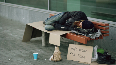 Young homeless drunk man preparing to sleep on cardboard on bench at the sidewalk Stock Photo