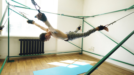 Young man doing exircise on quartering yoga equipment and pull his arms and legs with special ropes