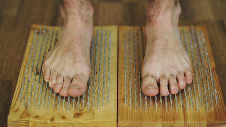 Closeup of yoga man stand on the board with sharp nails