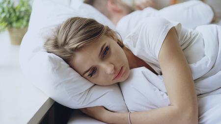 落ち込んだ若い女性がベッドに横たわり、自宅で寝ている彼女のボーイフレンドと口論した後、動揺した 写真素材