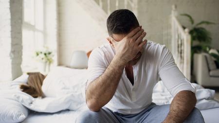 Jeune homme assis dans son lit contrarié a des problèmes avec le sexe tandis que sa copine dort dans la chambre à la maison Banque d'images - 91991334