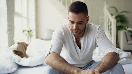 Contrarié jeune homme assis dans son lit souffre de problèmes alors que sa copine dort dans la chambre