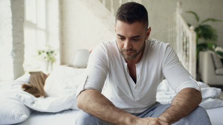 Upset young man sitting in bed suffer of problems while his girlfriend sleep in bedroom Standard-Bild