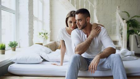 Gedeprimeerde jonge mensenzitting in bed die hebben benadrukt terwijl zijn meisje hem komt omhelzen en thuis kussen in slaapkamer