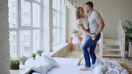 pareja joven y bella bailando bailando bailando bailando en la cama en la mañana en casa