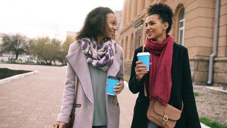 2人の美しい混合レースの女性の友人は、買い物や街の通りを歩く後にコーヒーを飲み、話します