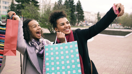 Two cute african american woman taking selfie with shopping bags and smiling. Friends have fun after visiting mall sale. Stock Photo